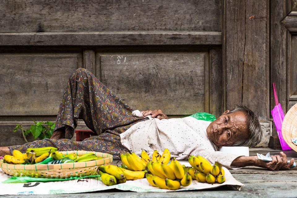 85 let, stále pracující, stále prodávající banány na chodníku Hoi An
